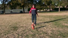 Kid Kicking American Football In Park Stock Footage