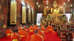 Buddhist monks pray in temple Stock Footage