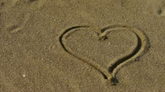 Heart on golden sandy beach,wind blow sand. Stock Footage