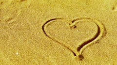 Heart on sandy beach,wind blow sand. Stock Footage