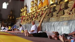 People sits under golden buddha statues Stock Footage