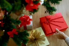 Hand taking gifts from under christmas tree NTSC - stock footage