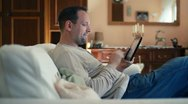 Young happy man with tablet computer sitting on sofa HD Stock Footage