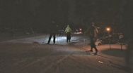 Stock Video Footage of Night Skier Family Passes by Cross Country Torchlit Trail