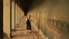 Woman in corridor of Angkor Wat watching mural Stock Footage