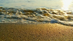 Sea waves on the beach at sunset close up Stock Footage