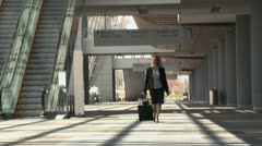 Caucasian businesswoman walking through airport with bags Stock Footage