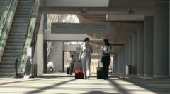Business travelers walking through airport with bags Stock Footage