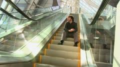 Caucasian businessman sitting on ascending escalator Stock Footage