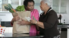 African American mother and daughter looking at groceries in kitchen Stock Footage