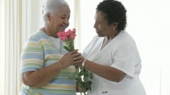 African American nurse giving bouquet of roses to senior patient Stock Footage