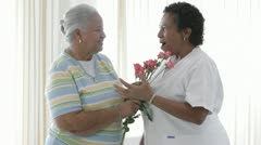 African American woman giving nurse bouquet of roses Stock Footage