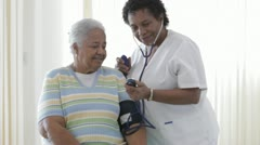 African American nurse taking senior patient's blood pressure Stock Footage