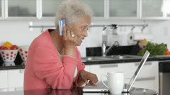 Senior African American woman at computer with credit card Stock Footage