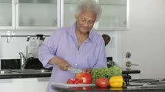 Senior African American woman cutting vegetables Stock Footage