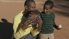 African American father playing baseball with son Stock Footage