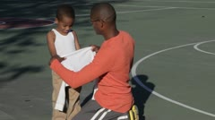 African American father helping son put on shirt Stock Footage