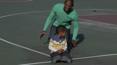 African American father on basketball court with son Stock Footage