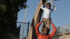 African American boy standing on father's shoulders Stock Footage