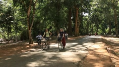 Couple riding bicycle on Angkor Wat road Stock Footage