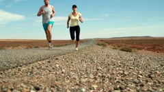 Young couple jogging on the road, slow motion, dolly shot HD Stock Footage