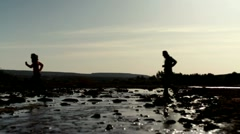 Silhouette of man and woman running across stream, slow motion HD - stock footage