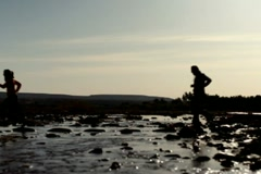 Silhouette of man and woman running across stream, slow motion NTSC Stock Footage