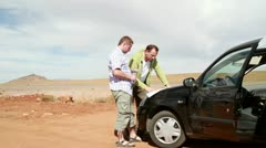 Two young male friends looking at a map on the car hood HD Stock Footage