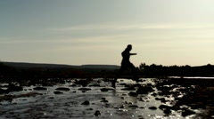 Silhouette of man running across stream, slow motion HD Stock Footage
