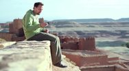 Man taking photo of himself with cellphone while sitting on ancient wall HD Stock Footage