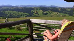 Woman on porch looking at mountain Stock Footage