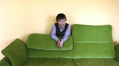 Boy behind couch laughing - stock footage