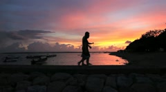Young couple walking along a beach at sunset in silhouette - stock footage