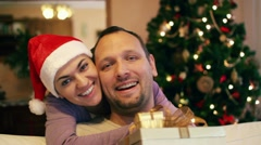 Young couple with gifts, Christmas tree in background HD Stock Footage