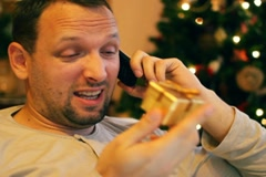 Disappointed man with little gift talking on cellphone NTSC Stock Footage