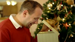 Happy man looking at great gift in the box, christmas tree in background HD Stock Footage