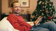 Stock Video Footage of Man with tablet computer smiling to camera, christmas tree in background HD