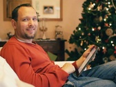 Stock Video Footage of Man with tablet computer smiling to camera, christmas tree in background NTSC