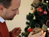 Stock Video Footage of Man decorating Christmas tree and smiling to camera NTSC