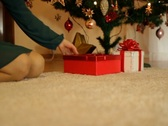 Stock Video Footage of Woman putting gifts under christmas tree, dolly shot NTSC