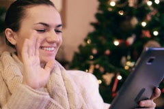 Woman chatting on tablet computer, christmas tree in background NTSC Stock Footage