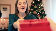 Stock Video Footage of Young happy woman gets present, christmas tree in background HD