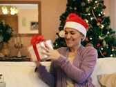 Stock Video Footage of Young woman in santa cap gets present, christmas tree in background NTSC