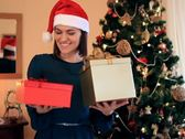 Stock Video Footage of Happy woman offering gift boxes, christmas tree in background NTSC