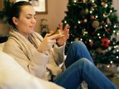 Stock Video Footage of Happy woman opening gift box, christmas tree in background NTSC