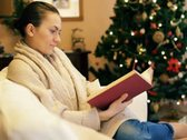 Stock Video Footage of Woman reading book on sofa, christmas tree in background NTSC