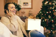 Woman talking on cellphone and looking at christmas gift NTSC Stock Footage