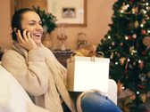 Stock Video Footage of Woman talking on cellphone and looking at christmas gift NTSC