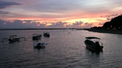 Fishing boats at sunset by a beach in Asia - stock footage