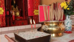 Incense and candles burning at a shrine in an Asian Taoist temple - stock footage